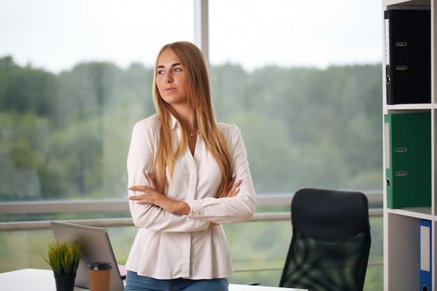 Junge schöne geschäftsfrau, die am laptop im hellen modernen büro arbeitet