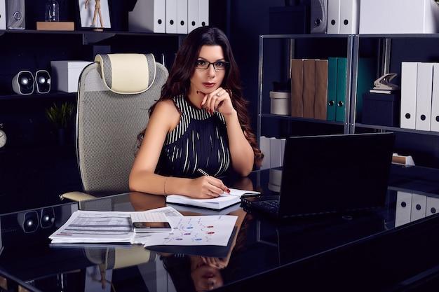 Junge schöne geschäftsfrau, die am stilvollen schwarzen schreibtisch arbeitet