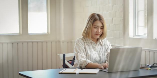 Junge schöne geschäftsfrau, die auf laptop-computer schreibt