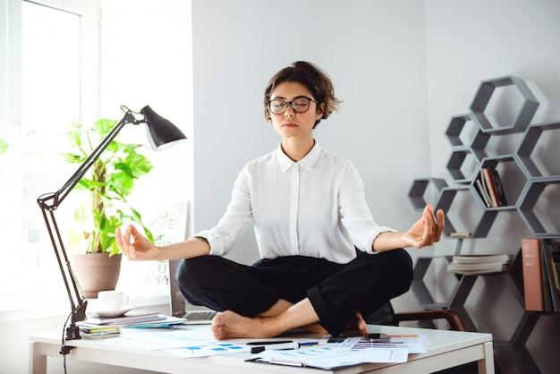 Junge schöne geschäftsfrau, die auf tisch am arbeitsplatz im büro meditiert.