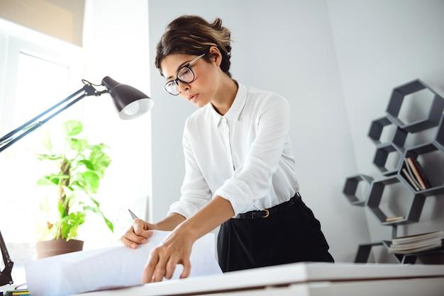Junge schöne geschäftsfrau, die durch papiere am arbeitsplatz im büro sortiert.