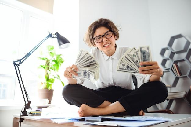Junge schöne geschäftsfrau, die geld hält, sitzt auf tisch am arbeitsplatz.