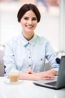 Junge schöne geschäftsfrau, die im städtischen café sitzt.