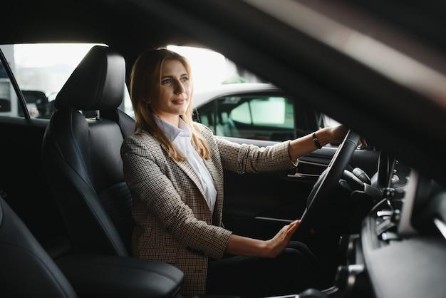 Junge schöne geschäftsfrau, die in ihrem auto sitzt
