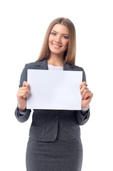 Junge schöne geschäftsfrau, die leeres blatt papier für kopienraum hält