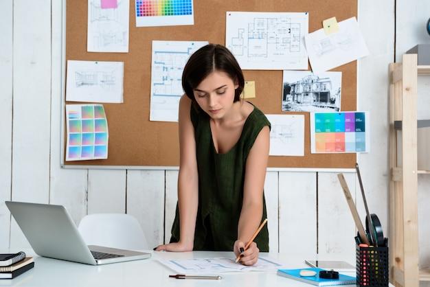 Junge schöne geschäftsfrau, die mit zeichnungen am arbeitsplatz arbeitet