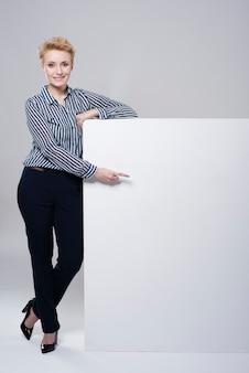 Junge schöne geschäftsfrau, die nahe breites leeres blatt papier lokalisiert aufwirft