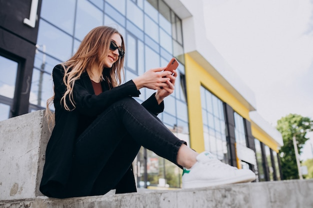 Junge schöne geschäftsfrau durch das bürozentrum, mit telefon