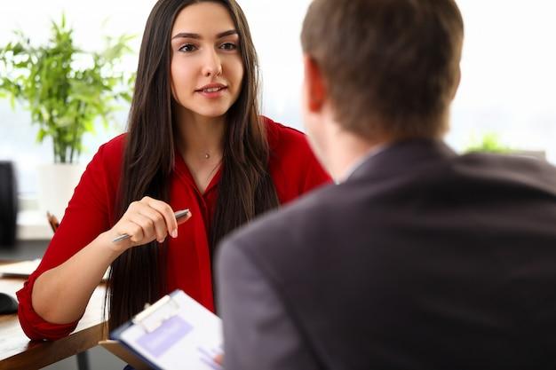 Junge schöne geschäftsfrau in der stilvollen offiziellen kleidung, die im büro sitzt und mit mannkollege spricht. geschäftsleute, verhandlungen, leute, die im bürokonzept arbeiten