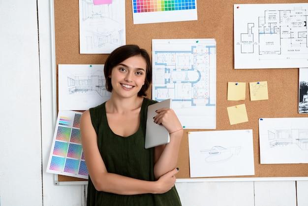 Junge schöne geschäftsfrau lächelnd, nahe schreibtisch mit zeichnungen stehend