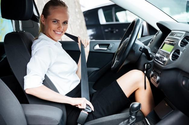 Junge schöne geschäftsfrau schnallt sich beim sitzen im auto an