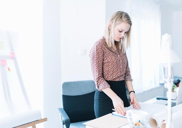 Junge schöne geschäftsfrau, welche die dokumente im büro überprüft