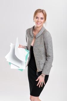 Junge schöne geschäftsfraublondine im schwarzen kleid, jacke, die einen ordner der papiere hält und auf grauem hintergrund lächelt