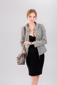Junge schöne geschäftsfrauenblondine im schwarzen kleid, in der jacke und im geldbeutel auf grauem hintergrund