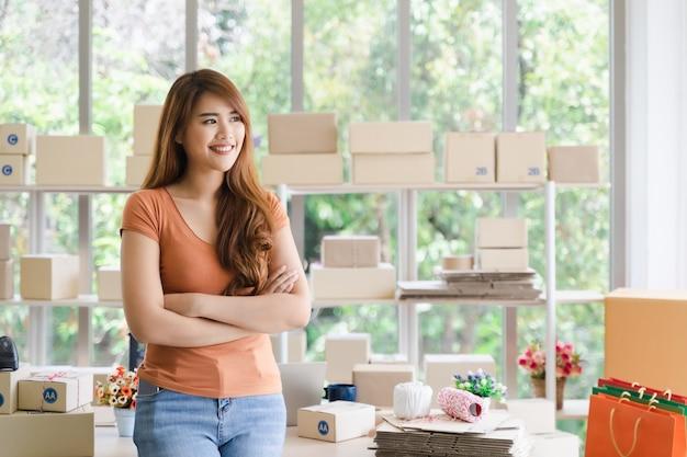 Junge schöne glückliche asiatische erfolgreiche geschäftsfrau mit smiley steht mit den armen, die in ihrem startinnenministerium, frau im guten gefühl mit geschäftserfolg, lieferungsverkäuferkonzept gekreuzt werden