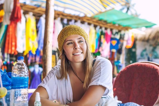 Junge schöne glückliche frau, die im café auf dem sommerstraßenmarkt im gelben hut sitzt