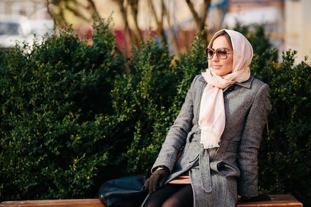 Junge schöne glückliche frau in einem mantel, der auf einer bank im park sitzt