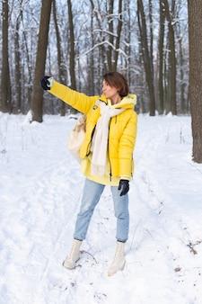 Junge schöne glückliche fröhliche frau im winterwald-videoblog, macht ein selfie-foto