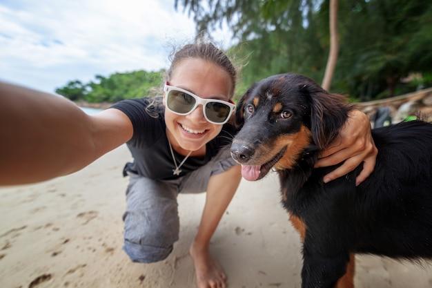 Junge schöne glückliche frohe mädchenfrau, die spaß hat, ein selfie an einem handy mit ihrem hund auf dem strand entlang dem sand zu nehmen