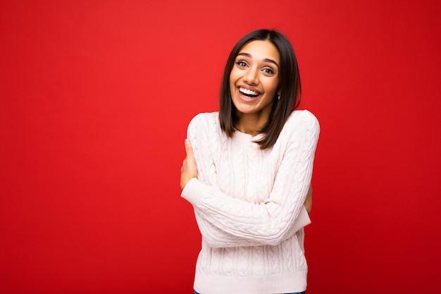 Junge schöne glückliche lächelnde brünette frau, die trendy helltrikot sexy sorglos trägt Premium Fotos