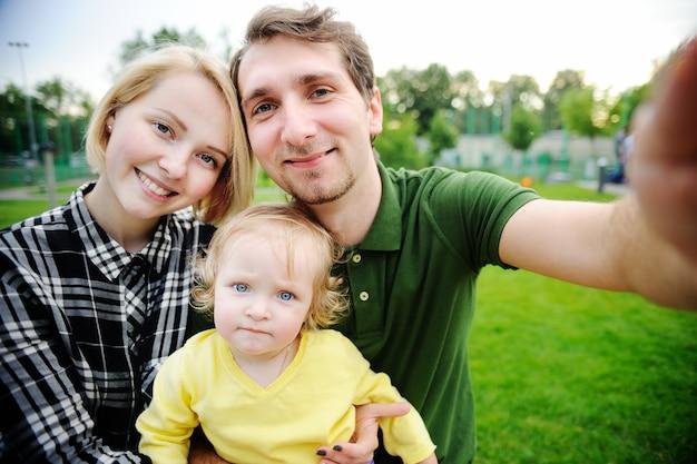 Junge schöne glückliche liebevolle familie, die zusammen selfie foto macht