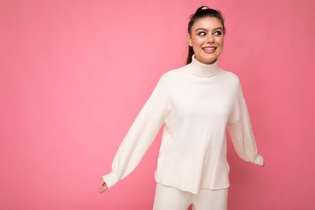 Junge schöne glückliche positive lächelnde stilvolle brünette frau, die beiläufige weiße strickjacke trägt