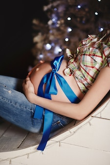 Junge schöne glückliche schwangere frau mit einem blauen bogen als geschenk