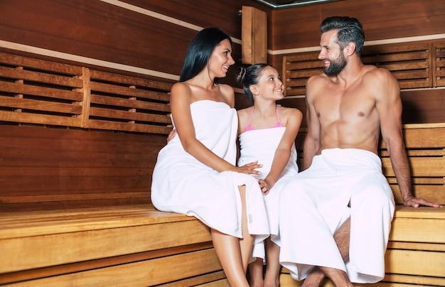 Junge schöne glückliche vater und mutter mit kleiner süßer tochter in den badetüchern entspannen in der heißen sauna