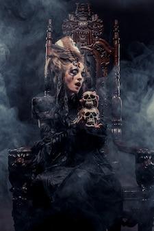Junge schöne hexe sitzt auf einem stuhl. helles make-up, schädel, rauch-halloween-thema.