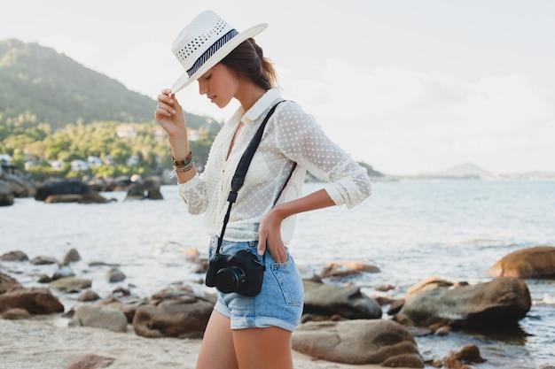 Junge schöne hipster-frau im sommerurlaub in asien, entspannend am tropischen strand, digitale fotokamera, lässiger boho-stil, seelandschaft, schlank gebräunter körper, reisen allein