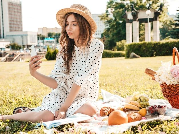 Junge schöne hipster-frau in trendigen sommerjeans, rosa t-shirt und hut. sorglose frau, die draußen picknick macht.