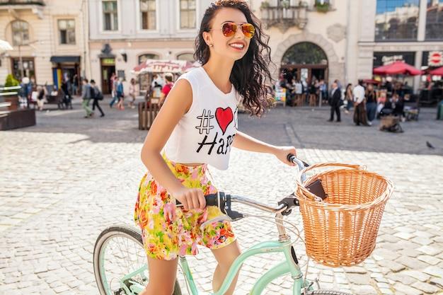 Junge schöne hipsterfrau, die auf fahrrad auf alter stadtstraße reitet