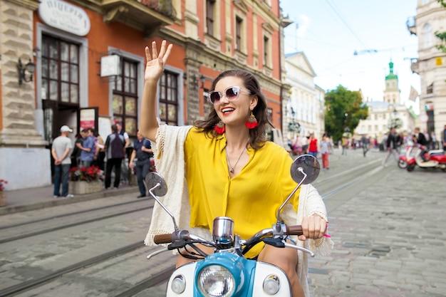 Junge schöne hipsterfrau, die auf motorradstadtstraße reitet