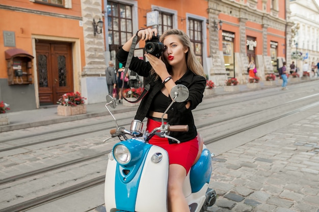 Junge schöne hipsterfrau, die mit fotokamera auf motorradstadtstraße reitet