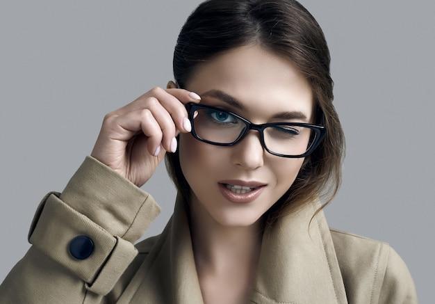Junge schöne hipsterfrau im modischen mantel und in den gläsern