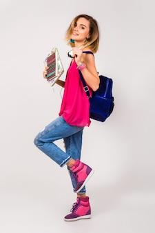 Junge schöne hipsterfrau, rosa schuhe und top, die bücher halten