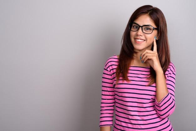 Junge schöne indische frau, die brillen gegen graue wand trägt