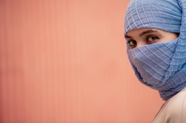 Junge schöne islamische frau mit ihrem gesicht versteckt hinter blauem hijab, der sie isoliert betrachtet