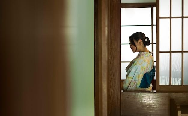 Junge schöne japanische frau, die einen traditionellen kimono trägt