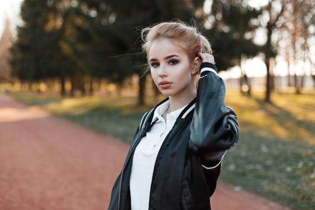 Junge schöne junge blonde frau mit braunen augen in einem stilvollen weißen hemd in einer modischen hellschwarzen jacke auf grünen bäumen und sonnenuntergang im park. nettes mädchen geht im freien. Premium Fotos