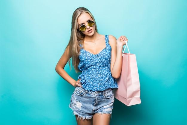 Junge schöne junge frau mit farbigen einkaufstaschen über blauem hintergrund