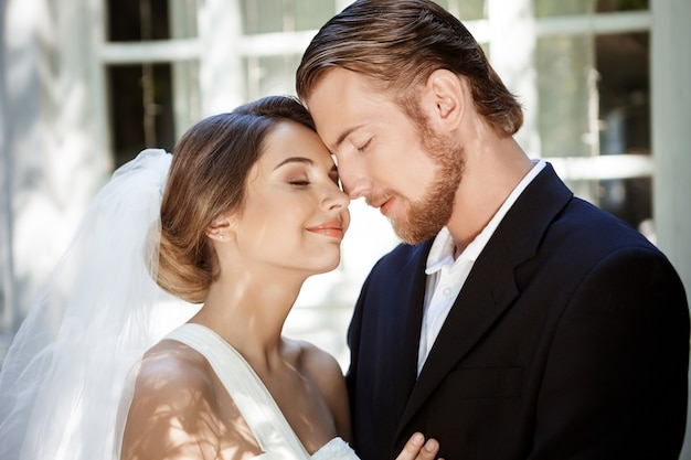 Junge schöne jungvermählten, die mit geschlossenen augen lächeln und genießen.