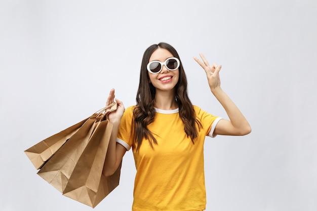 Junge schöne käuferfrau mit einkaufstüten zeigt zwei finger