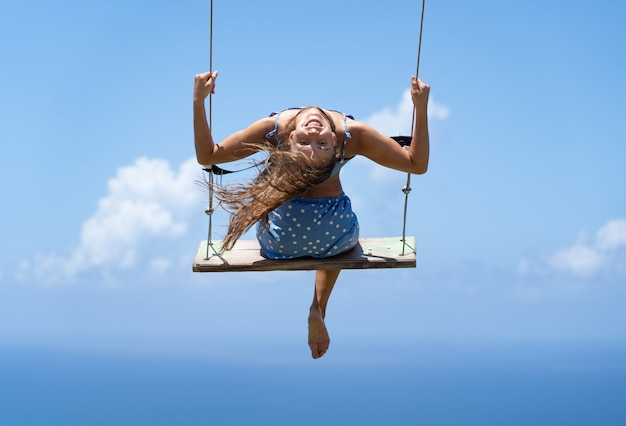 Junge schöne kaukasische frau auf der seilschaukel mit meer- und himmelshintergrund. konzept von freiheit und glück.
