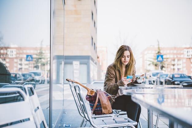 Junge schöne kaukasische frau, die auf einer stange hat einen tasse kaffee sitzt