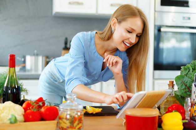 Junge schöne kaukasische frau, die ihr digitales tablett in der küche kocht und verwendet