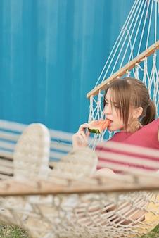 Junge schöne kaukasische frau, die in der hängematte draußen liegt und scheibe der reifen wassermelone am sommernachmittag isst