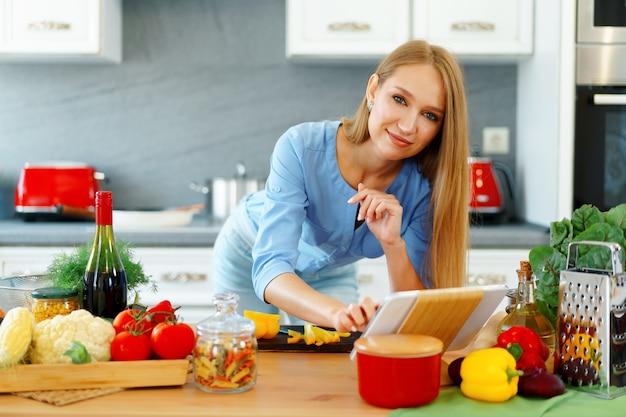 Junge schöne kaukasische frau, die kocht und ihr digitales tablett in der küche zu hause verwendet