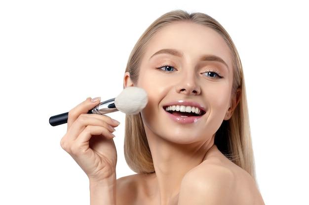 Junge schöne kaukasische frau, die make-up anwendet. lächelnde frau mit puderpinsel isoliert