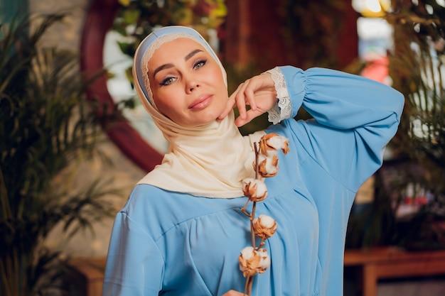 Junge schöne kaukasische frau, die traditionelles muslimisches kopftuch im hipster-café mit großen fenstern in voller länge trägt. frau im blauen hijab im gemütlichen café. hintergrund, kopierraum, nahaufnahmeporträt.